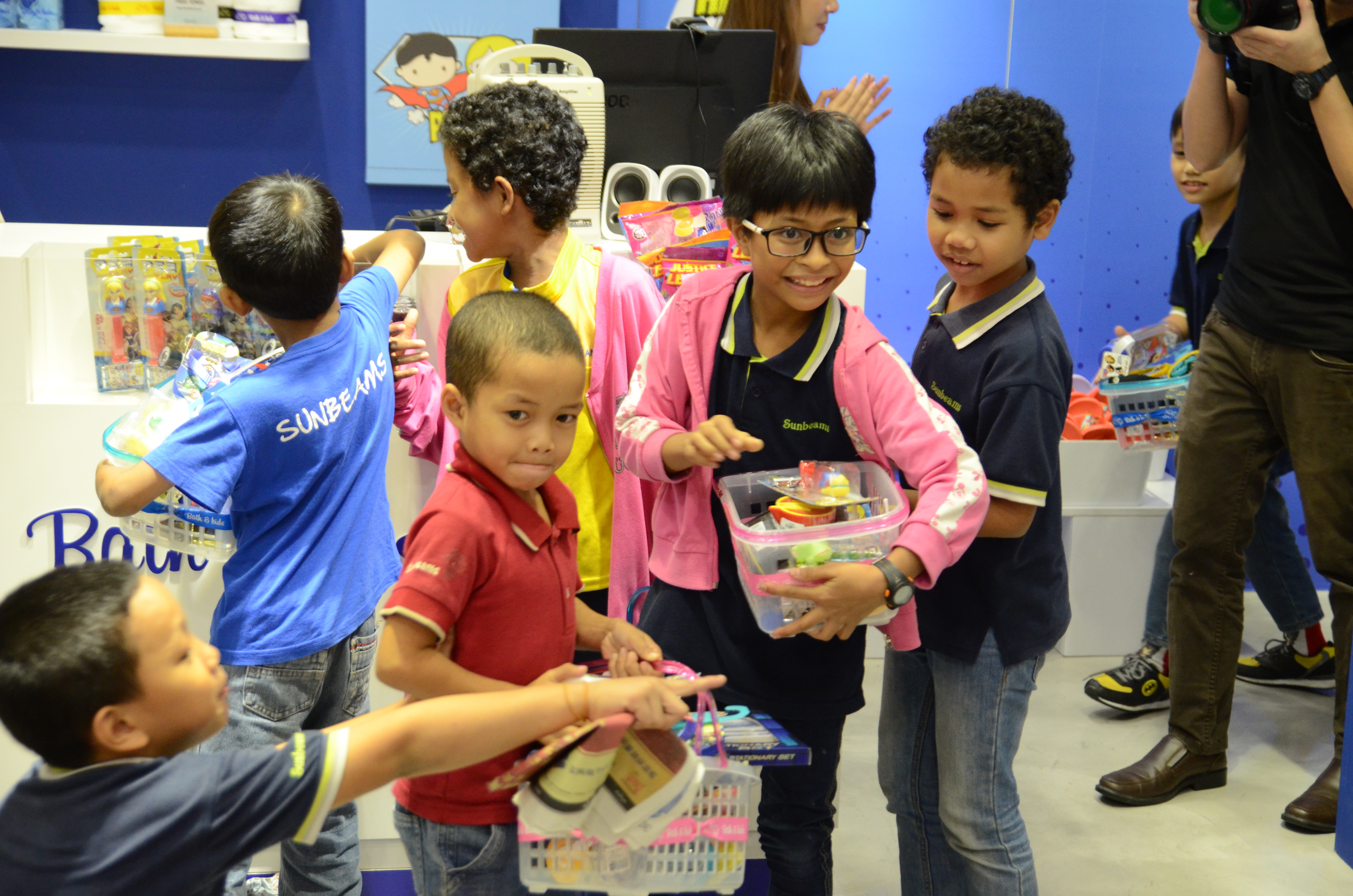 Children of Yayasan Sunbeams Home filling up their shopping baskets with Justice League products at Bath & Kids, 1Utama