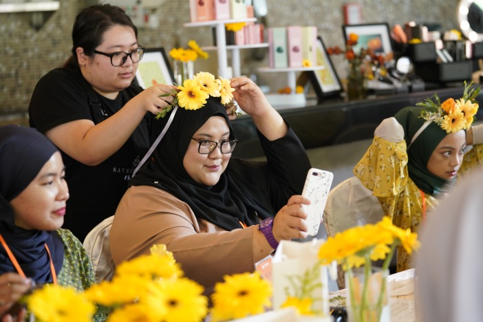 Participants putting on their own creation of the Calendula Crown